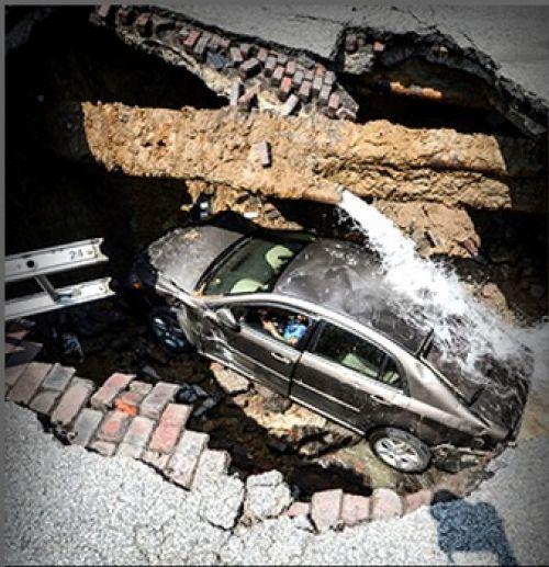 Una mujer y su auto, atrapados en un hueco callejero (Video)