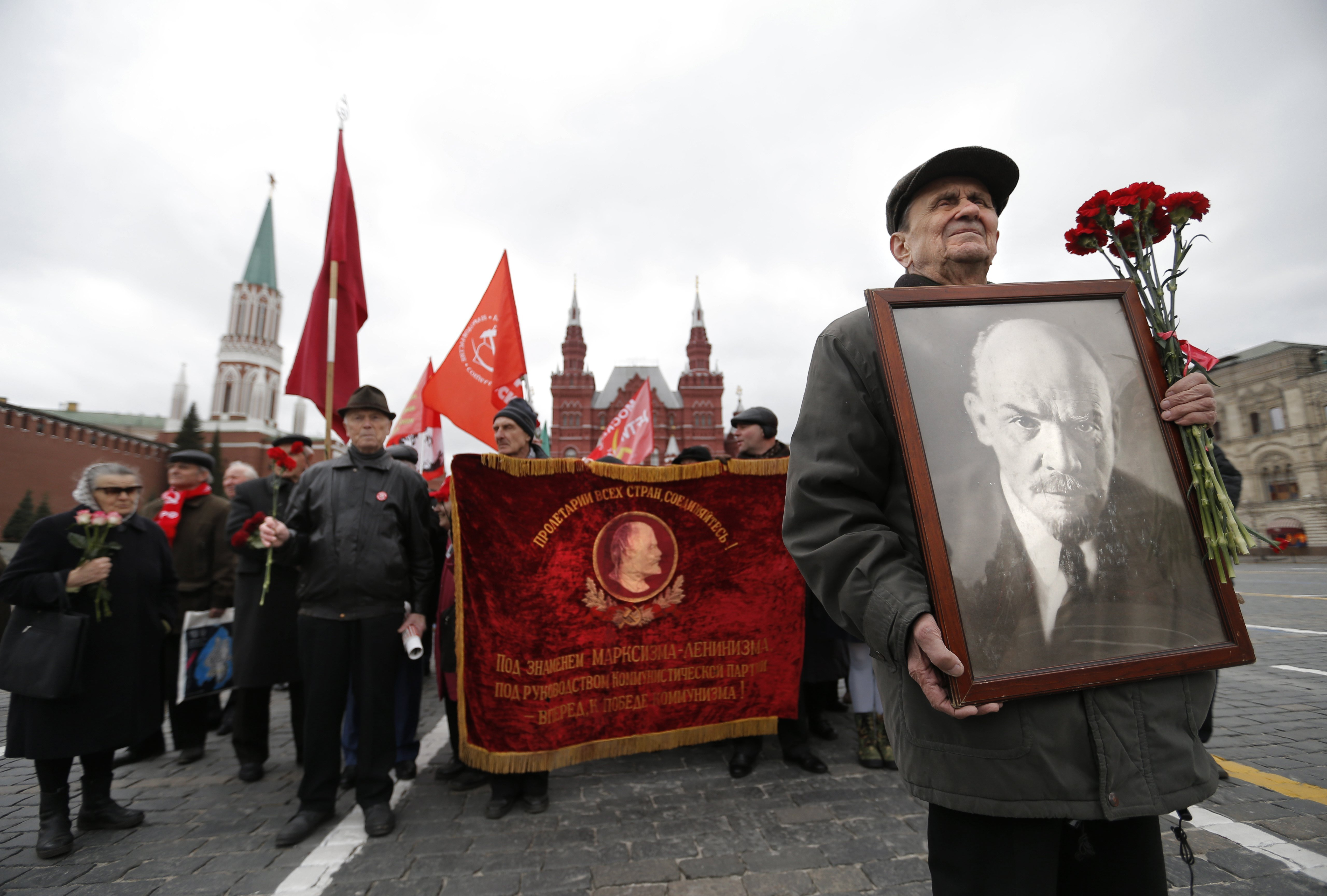 SHP08. Moscow (Russian Federation), 22/04/2017.- Members of Russian Communist party hold flags and Lenin's portrait as they stand in line to visit Lenin's mausoleum on the Red square in Moscow, as they celebrate the 147st anniversary of his birthday, Moscow, Russia, 22 April 2017. Vladimir Lenin, a founder of the Russian Communist party and father of the communist revolution in Russia is buried as a mummy on the central capital square. There have been demands to rebury Lenin next to his mother at Volkovo cemetery in St. Petersburg, according to what has been said was his will. In 2017, Russians will mark the 100th anniversary of the 'Great October Socialist Revolution', or 'Bolshevik Revolution' of 1917. (San Petersburgo, Moscú, Rusia) EFE/EPA/MAXIM SHIPENKOV